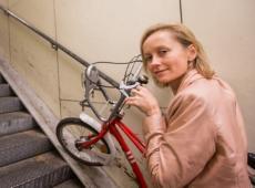 Annick De Ridder met Antwerps stadsfietsje in de hand op de moeilijk toegankelijke trappen van de Kennedy fietserstunnel